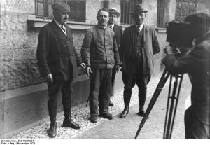 Zu dem kommenden Riesenprozeß gegen den Massenmörder Haarmann , welcher 27 Morde in Hannover vollbrachte. Zu dem Prozeß sind über 190 Zeugen geladen und ist mit einer Prozeßdauer von 14 Tagen zu rechnen. Der Massenmörder Haarmann in Ketten gehalten durch Kriminalbeamte, wird gefilmt.